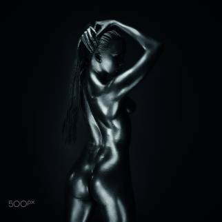Young fit athletic woman in silver body paint posing